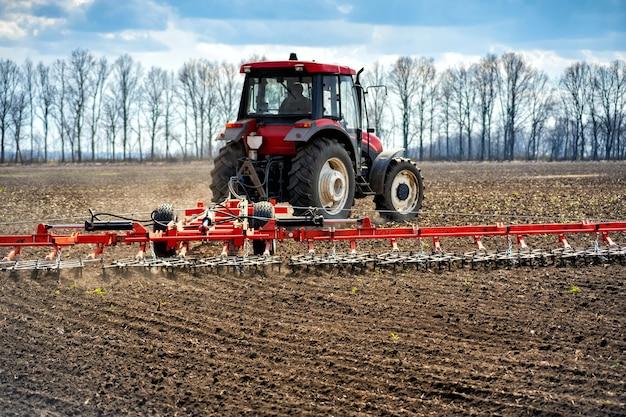 Lavorazione in campo con trattore con macchina trainata.