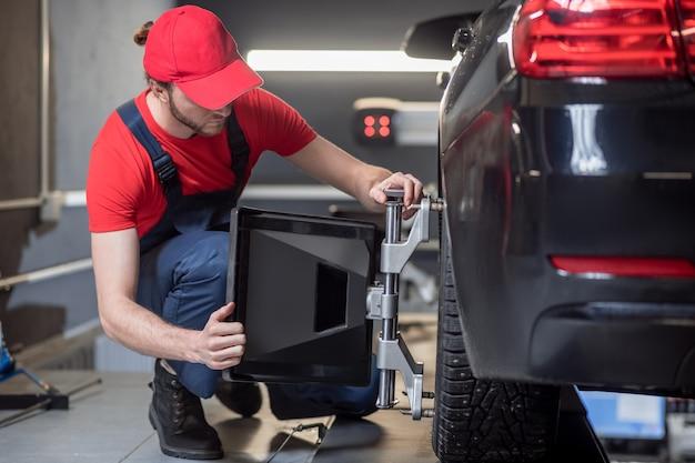 Allineamento dell'angolo di inclinazione. giovane uomo adulto in abiti da lavoro che raddrizza la ruota accovacciato vicino all'automobile in officina