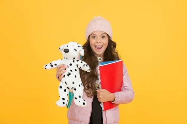 Tempo di pausa e relax. felicità dell'infanzia. cura e sviluppo del bambino. libri per la cura dei bambini. vita quotidiana dell'alunno. di nuovo a scuola. felice piccola ragazza tenere il cane giocattolo. vacanze invernali e vacanze.