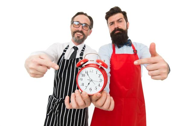 È ora di cucinare. uomini che puntano alla sveglia. uomo barbuto hipster e chef maturo grembiule sfondo bianco. cucina la cena. cuciniamo subito. i colleghi degli amici iniziano a cucinare appena in tempo.