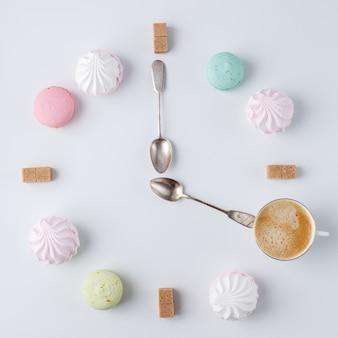 È ora di bere il caffè. un orologio a forma di caffè. macarons, zucchero, marshmallow. lavoro creativo e creativo.