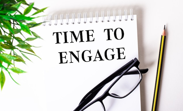 Time to engage è scritto in un taccuino bianco accanto a una matita, occhiali con cornice nera e una pianta verde