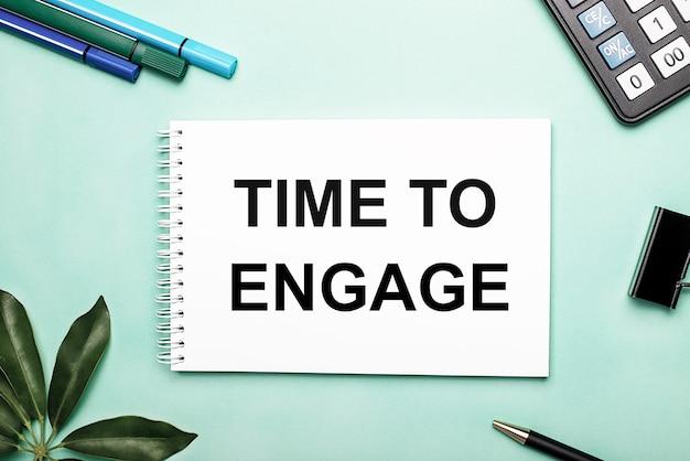 Time to engage è scritto su un foglio bianco su una superficie blu vicino alla cancelleria e al foglio scheffler. chiamare all'azione