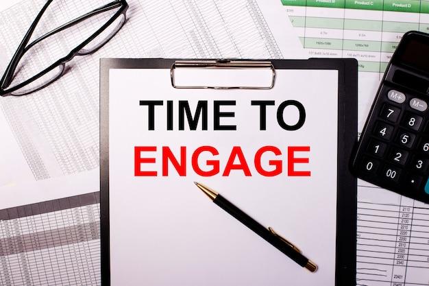 Time to engage è scritto su un foglio di carta bianco, vicino ai bicchieri e alla calcolatrice.
