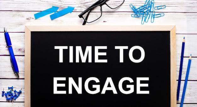 Time to engage scritto su un blocco note nero accanto a graffette blu, matite e una penna.
