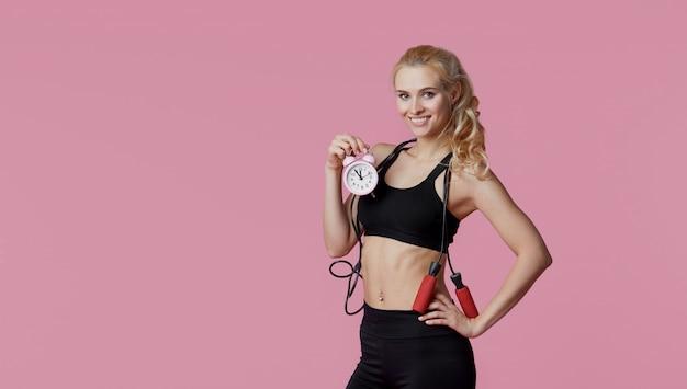 Tempo per il fitness. la giovane vettura scioccata della donna di sport tiene la sveglia rosa a disposizione