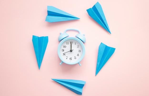 Concetto di volo di tempo con aeroplani di carta blu e sveglia su una superficie rosa.