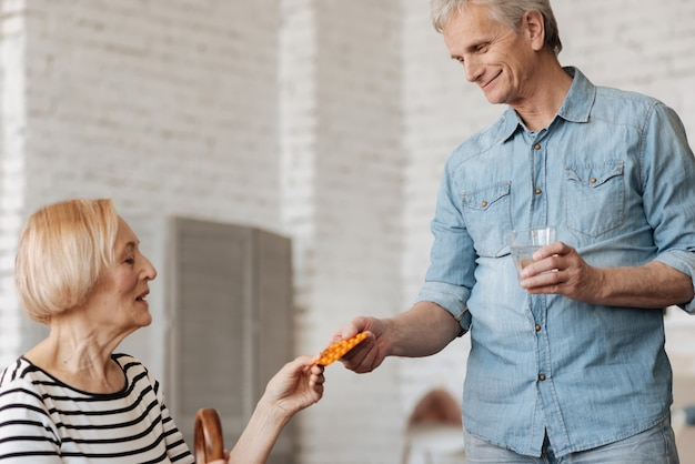 È ora di stare meglio. ammirabile bel signore anziano che dà a sua moglie le pillole di cui ha bisogno per riprendersi da una malattia recente