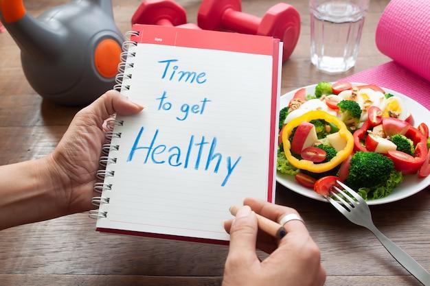 È tempo di stare bene, testo sul libro del diario con insalata e articoli per il fitness sul tavolo