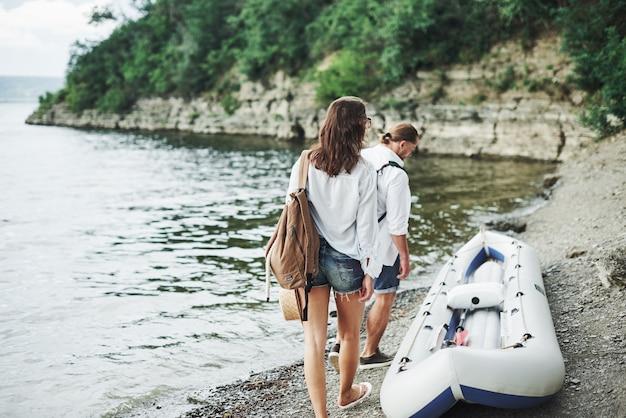 Tempo di andare. i turisti soddisfatti del viaggio che fanno sullo sfondo degli alberi vicino alla barca.