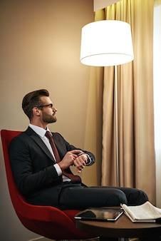 È ora di riposarsi. uomo d'affari in attesa di qualcuno sulla sedia rossa nella camera d'albergo. guarda il suo orologio da polso
