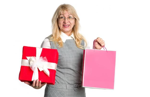 Tempo per lo shopping natalizio. la donna matura mostra il pacchetto rosa e il contenitore di regalo rosso. donna senior con regali.