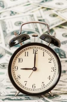 Il tempo è denaro, orologi sotto sfondo di dollari americani.