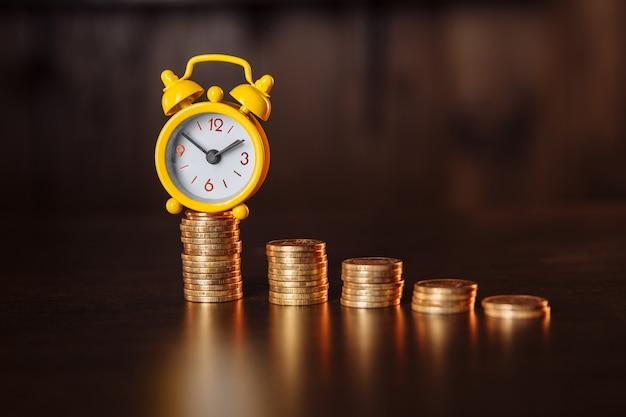 Il tempo è il concetto di denaro. una sveglia e una pila di monete su un tavolo di legno.
