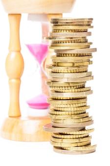 Il tempo è denaro concetto - monete e clessidra