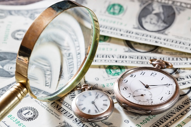 Il tempo è denaro concetto di finanza con vecchi orologi vintage, banconote da un dollaro e lente d'ingrandimento