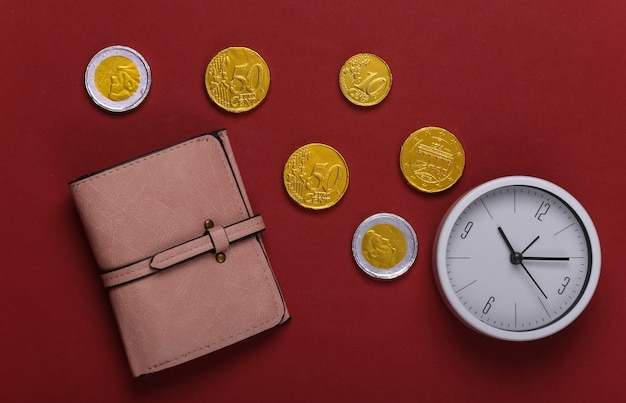 Il tempo è denaro. portafoglio in pelle con monete e orologio su rosso