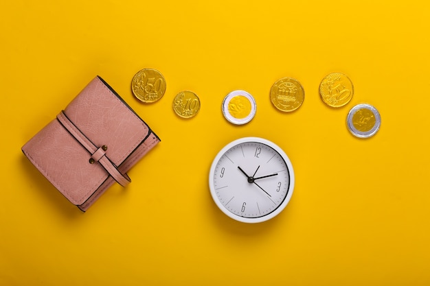 Il tempo è denaro. portafoglio in pelle con monete e orologio su giallo