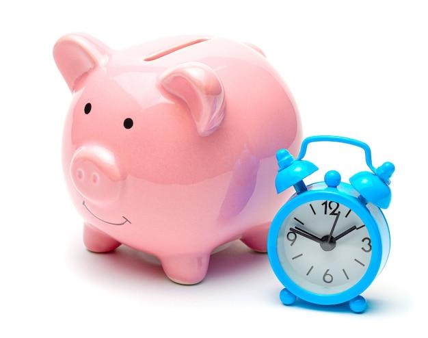 Il tempo è denaro. salvadanaio e orologio con sveglia.