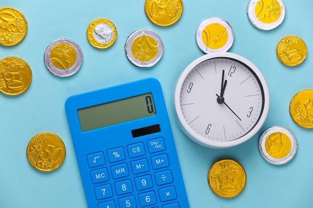 Il tempo è denaro. orologio bianco con calcolatrice e monete su blu