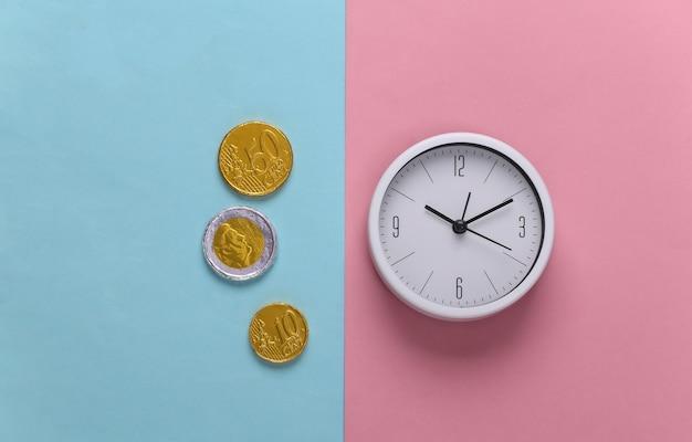 Il tempo è denaro. orologio bianco con monete su rosa pastello blu
