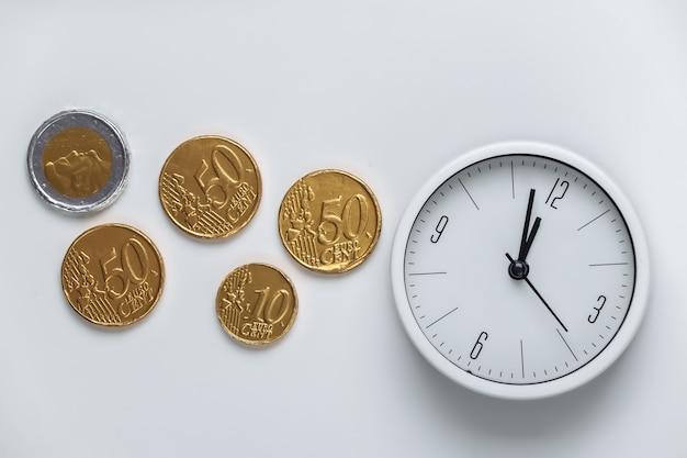 Il tempo è denaro. orologio bianco con monete su bianco