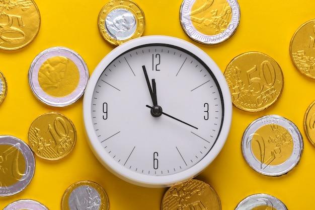 Il tempo è denaro. orologio bianco con monete su giallo