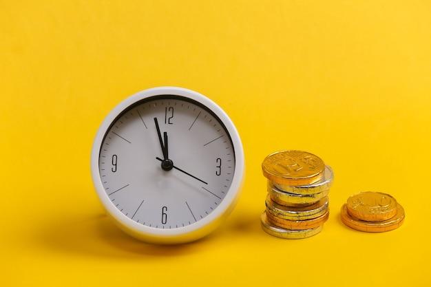Il tempo è denaro. orologio bianco con una pila di monete su giallo