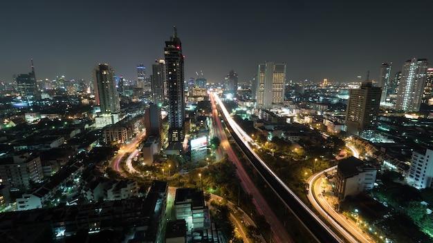Colpo di lasso di tempo della vita notturna nell'incrocio di traffico grattacielo illuminato grande città bangkok thailand