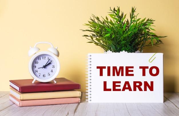 Time to learn è scritto in un quaderno accanto a una pianta verde e una sveglia bianca, che si trova su agende colorate.