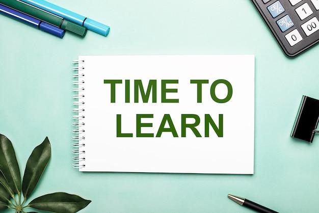Time to learn è scritto su un foglio bianco su una parete blu vicino alla cancelleria e al foglio scheffler. chiamare all'azione. concetto motivazionale