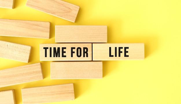 Time for life testo scritto su blocchi di legno su sfondo giallo