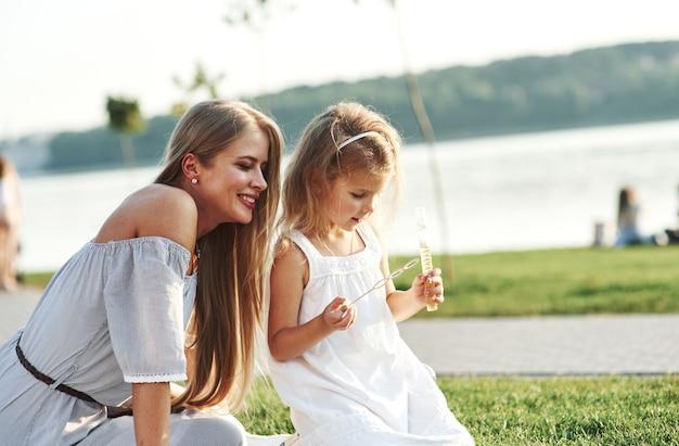 Tempo per piccole scoperte. da dove vengono queste bolle. foto di giovane madre e sua figlia che si divertono sull'erba verde con il lago sullo sfondo.