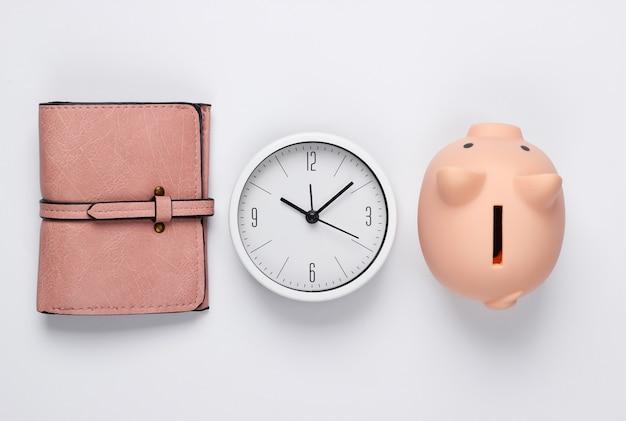 È ora di fare soldi. depositare. orologio bianco, salvadanaio e portafoglio su sfondo bianco. colpo minimalista dello studio. vista dall'alto