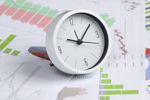 È ora di fare soldi, investire. grafici e grafici e orologio. concetto di affari. vista dall'alto