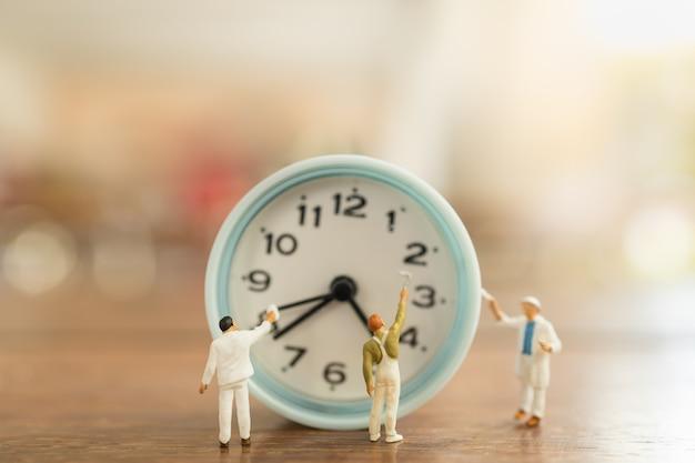 Concetto di gestione del tempo. chiuda su del gruppo di figure miniatura della gente del lavoratore pulite e dipingono l'orologio rotondo d'annata sulla tavola di legno.