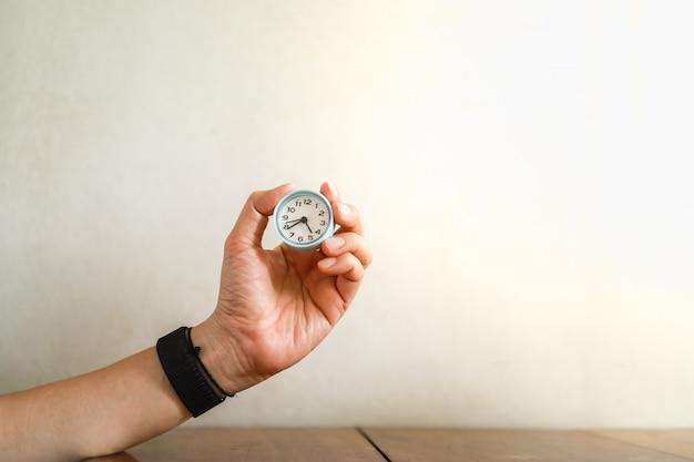 Concetto di gestione del tempo. chiuda su dell'orologio rotondo d'annata della tenuta della mano dell'uomo sulla tavola di legno con lo spazio della copia.
