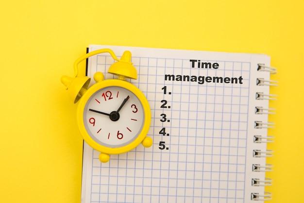 Concetto di gestione del tempo. apri un piccolo taccuino con l'elenco delle cose da fare e la sveglia gialla a parte.