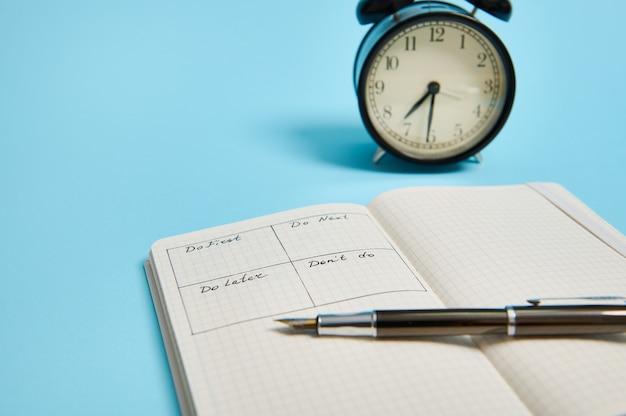 Gestione del tempo, concetto di scadenza: un taccuino organizzatore aperto con orario del giorno per ora, penna a inchiostro, sveglia su sfondo a colori, spazio di copia. immagine ritagliata