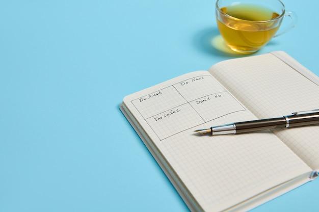 Gestione del tempo, concetto di scadenza: un taccuino organizzatore aperto con orario del giorno per ora, penna a inchiostro, una tazza da tè su sfondo a colori, spazio di copia. immagine ritagliata