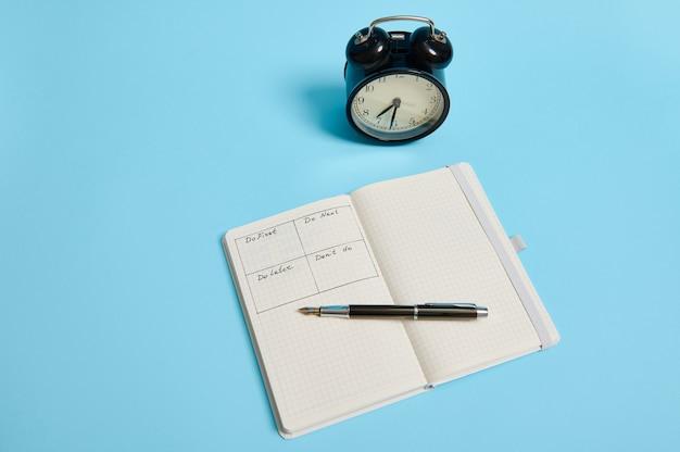 Gestione del tempo, scadenza e concetto di corretta pianificazione e organizzazione del tempo: un taccuino organizzatore aperto con orario del giorno per ora, penna a inchiostro, sveglia su sfondo colorato, spazio per le copie.