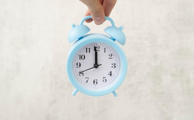 Gestione del tempo, puntualità, concetto di risveglio. un uomo irriconoscibile tiene in mano una piccola sveglia blu