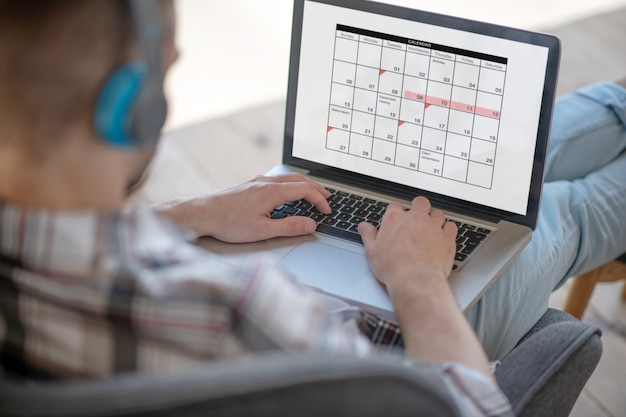 Menegement del tempo. un giovane uomo d'affari che controlla il suo calendario di lavoro in linea