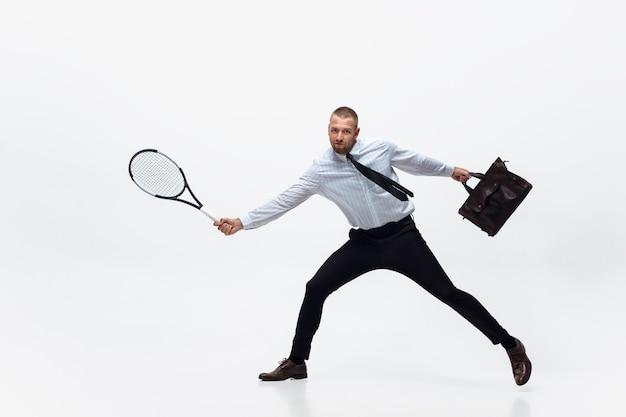 Tempo per il movimento l'uomo in abiti da ufficio gioca a tennis isolato su sfondo bianco studio