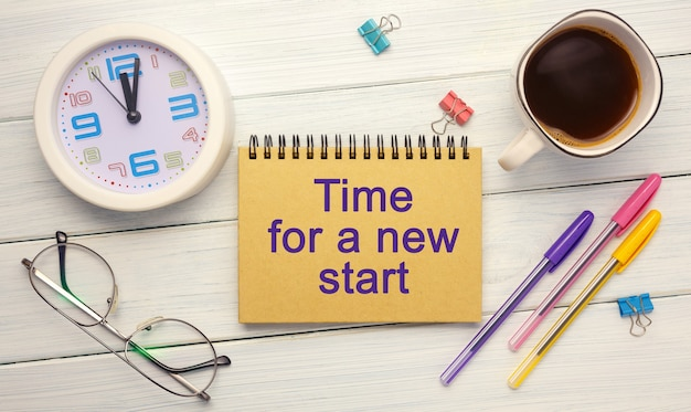 Tempo per un nuovo inizio scritto su un taccuino su un tavolo di legno con vista dall'alto di forniture per ufficio
