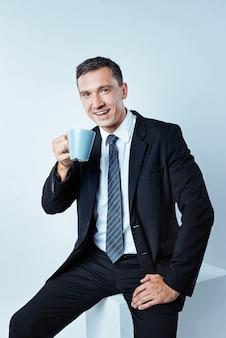 Tempo di rilassarsi. immagine ritagliata di un imprenditore maturo che indossa un abito nero che guarda nell'obiettivo e sorride mentre si ricarica le batterie con una tazza di caffè aromatico.