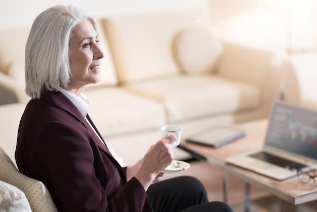 Tempo di rilassarsi. felice imprenditrice invecchiata allegra sorridendo e bevendo un caffè mentre era seduto in ufficio davanti al computer portatile ed esprimendo felicità