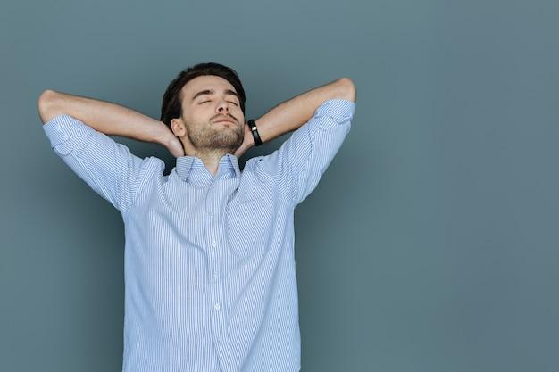 Tempo di rilassarsi. felice piacevole uomo sognante chiudendo gli occhi e dormendo mentre riposa dopo il lavoro