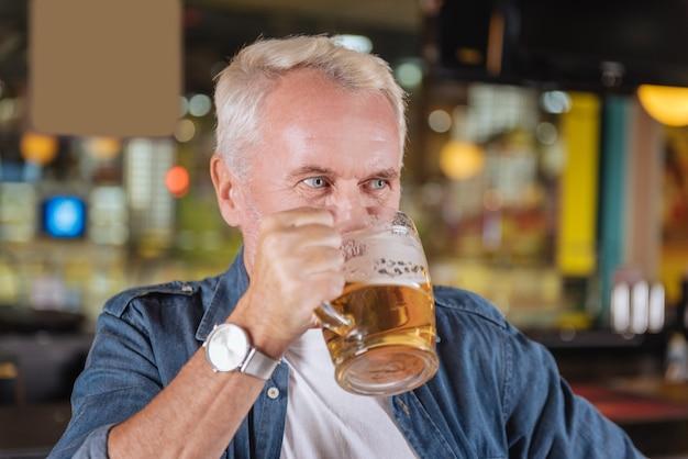 Tempo di rilassarsi. gioioso uomo anziano che visita un pub mentre riposa nei fine settimana