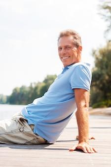 Tempo di rilassarsi. vista laterale di un uomo maturo felice che guarda lontano e sorride mentre è seduto in banchina